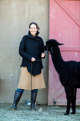 Rebecca with a friendly alpaca, wearing a water-resistant coat she made by hand.