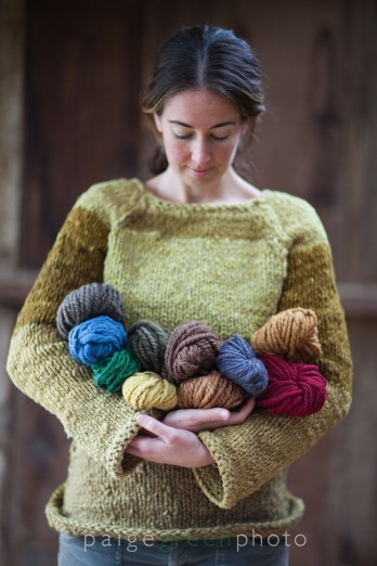 Rebecca Burgess with a hand-knit sweater dyed with coffeeberry, holding skeins of naturally dyed handspun wool.