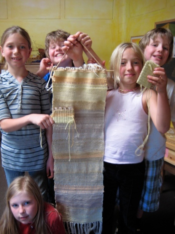 One of the many children's groups that Rebecca has taught about weaving and dyeing, with their handiwork.