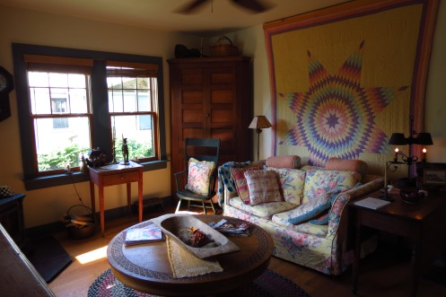 The living room is enlivened by an antique quilt and a round table, made by Susan's father.